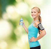 sport, excercise, technology, internet and healthcare - sporty woman listening to music from smartph