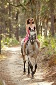 young woman riding horse bareback in forest