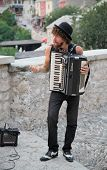MOSTAR, BOSNIA AND HERZEGOVINA - AUGUST 9, 2012: Street musician plays accordion. The streets of Mostar are the stage of the Arts Festival.