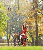 Smiling young female standing with bicycle in park and looking at camera, shot with a tilt and shift lens