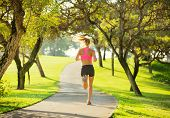 Athletic fit young woman jogging running outdoors early morning in park. Healthy lifestyle sports fi