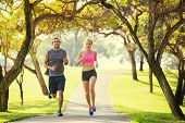 Couple jogging running outside in the park at sunrise on beautiful path. Healthy lifestyle fitness c