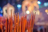 Red incense sticks burning in bokeh night