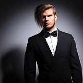 dramatic picture of a fashion elegant man in tuxedo and bow tie looking away from the camera