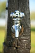 A stainless steel water tap drips water from its faucet during a drought in California outside. Shot