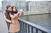Tourists couple taking pictures in city with a smartphones