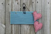 Antique blue sign with red hearts and iron keys hanging on wood door