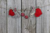 Red and wood hearts and cherry soda bottle caps hanging on clothesline with wood background