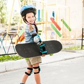 cute little girl in a helmet holding a skate in the park