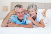 Portrait of loving senior couple lying in bed at home