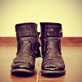 picture of a pair of worn and torn boots on the floor with a retro effect