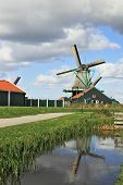 The village - an ethnographic museum in Holland. The picturesque windmill and a barn is reflected in