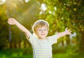 stock photo of open arms  - Smiling little boy with open arms in a summer garden - JPG