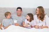 Portrait of happy man with family having breakfast in bed