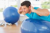 Side view of a young man exercising on fitness ball at a bright gym