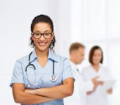 healthcare and medicine concept - smiling female african american doctor or nurse in eyeglasses with