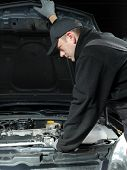 Auto mechanic inspecting car engine compartment