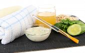 Homemade facial masks with natural ingredients, on bamboo mat, isolated on white