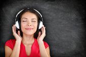 Music in headphones. Beautiful young Asian woman with her eyes closed in bliss listening to music wearing a set of headphones and standing against black blackboard background with copyspace