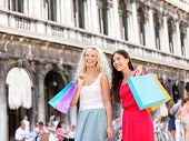Shopping women - girl shoppers holding shopping bags in Venice. Portrait of beautiful girlfriends smiling happy together having fun on San Marco Square, Venice, Italy. Caucasian and Asian models.