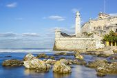 Long exposure image of the fortress of El Morro in the bay of Havana with rocks and silky water