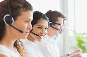 Portrait of smiling businesswoman with colleagues working in call center