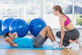 Side view of female trainer helping man with his exercises at a bright gym