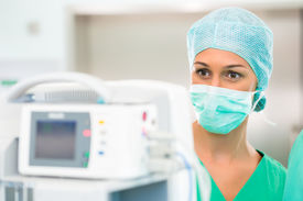 pic of operation theater  - Surgeon doctor in sterile operating room or operation theater checking data on heart monitor in emergency situation - JPG