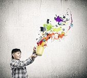 Cute boy splashing colorful paint from bucket
