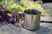 stock photo of ferrous metal  - metal cup of tea about flowers on wooden table - JPG