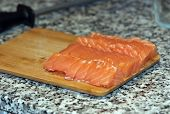 Fresh salmon fish with knife on wooden cooking desk
