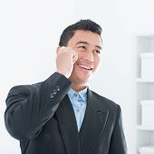 pic of southeast asian  - Southeast Asian business executive talking on smartphone in office background - JPG
