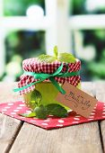Homemade mint jelly in glass jar, on wooden table, on bright background