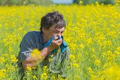 pic of hay fever  - man in field blowing his nose and suffering from hay fever - JPG