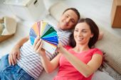 Happy young couple lying on the floor of new house and looking at colorful palette