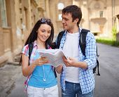 Couple of travelers studying map of ancient town