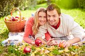 Happy young couple with ripe apples having rest in park