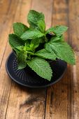 Chinese traditional bowl for tea with mint leaves on wooden background