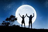 Silhouettes of young couple against full moon