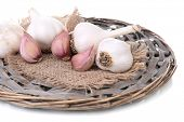 Fresh garlic on wicker mat isolated on white