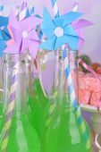Bottles with drink and sweets on bright background