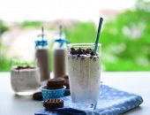 Milk cocktails in glasses and chocolate cookies on table on natural background