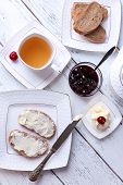 Fresh bread with cherry jam and homemade butter on plate on wooden background