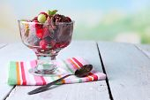 Chocolate ice cream with mint leaf and ripe berries in glass bowl, on color wooden table, on bright