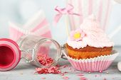 Tasty cup cake with cream on grey wooden table