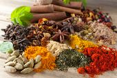Closeup of an assortment of colorful spices, herbs and teas on a wooden table