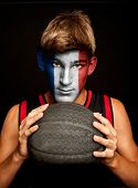 portrait of basketball player with french flag painted on his face