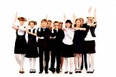 Schoolchildren stand together and raise hands up. Full length portrait. Isolated over white.