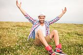 young casual man celebrates success in a field with hand in the air