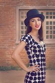 Happy young woman wearing top hat posing against vintage house.